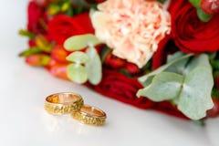 Goldeheringe auf einem weißen Hintergrund und einem Blumenstrauß einer Braut von den Rosen Lizenzfreie Stockfotos