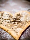 Goldeheringe liegen auf einem Naturholz Sawing mit Herzen Lizenzfreie Stockfotos