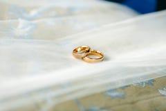Goldeheringe mit einem Diamanten auf dem Hintergrund des weißen Brautschleiers Lizenzfreie Stockfotografie