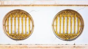 Goldeisenstange mit Kreisfenstern auf der defekten weißen Wand Stockfotografie