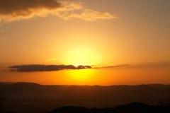 Golden. Sun setting behind a cloud stock photos