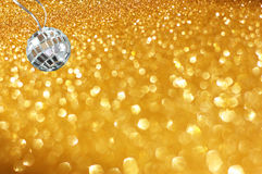 Golden abstract bokeh lights and miniature glitter ball. party or music concept. Royalty Free Stock Photos