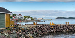 Golden adirondack chairs on a rock jetty.   Houses on the sea along a village shoreline. Royalty Free Stock Image