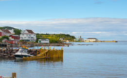 Golden adirondack chairs on a rock jetty.   Houses on the sea along a village shoreline. Royalty Free Stock Photography