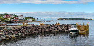 Golden adirondack chairs on a rock jetty.   Houses on the sea along a village shoreline. Stock Photo