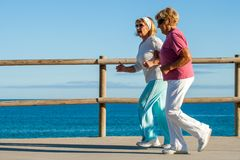 Golden agers running at seafront. Stock Images