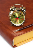 Golden alarm clock on the book Royalty Free Stock Image