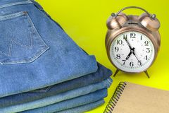 Golden alarm clock and jeans. On yellow background Stock Image