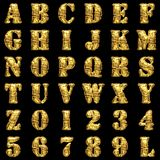 Golden alphabet on black background Stock Photo