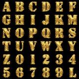 Golden alphabet on black background Stock Photo