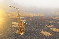 Golden Alto Saxophone Lies on the Black Background. Romantic and Beautiful Saxophone. Place for Text. The Etna volcano. The island stock photo
