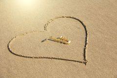 The golden alto saxophone lies inside the heart of the sand, on the beach. Romantic musical background. Musical cover and creative. Design with copy space stock photo
