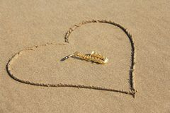 The golden alto saxophone lies inside the heart of the sand, on the beach. Romantic musical background. Musical cover and creative. Design with copy space royalty free stock photography