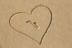 The golden alto saxophone lies inside the heart of the sand, on the beach. Romantic musical background. Musical cover and creative. Design with copy space stock images