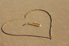 The golden alto saxophone lies inside the heart of the sand, on the beach. Romantic musical background. Musical cover and creative. Design with copy space stock photos