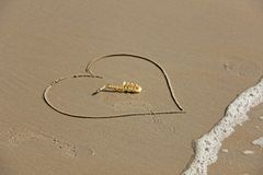 The golden alto saxophone lies inside the heart of the sand, on the beach. Romantic musical background. Musical cover and creative. The wave is washing away royalty free stock photography