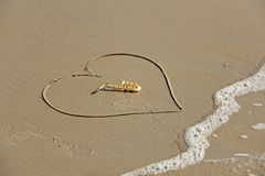 The golden alto saxophone lies inside the heart of the sand, on the beach. Romantic musical background. Musical cover and creative. The wave is washing away stock photography