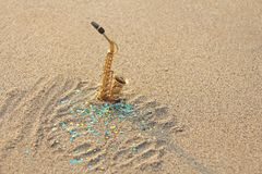 The golden alto saxophone stands on the sand against the background of blue shimmers. Romantic musical background. Musical. Cover, creative. Design with copy stock photography