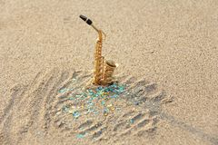 The golden alto saxophone stands on the sand against the background of blue shimmers. Romantic musical background. Musical. Cover, creative. Design with copy royalty free stock photography