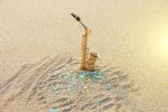 The golden alto saxophone stands on the sand against the background of blue shimmers. Romantic musical background. Musical. Cover, creative. Design with copy royalty free stock image