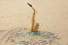The golden alto saxophone stands on the sand against the background of blue shimmers. Romantic musical background. Musical cover,. Creative. Design with copy royalty free stock images