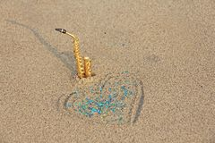 The golden alto saxophone stands on the sand next to the heart of sand and blue shining. Romantic musical background. Musical. Cover, creative. Design with copy royalty free stock image