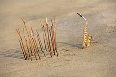 The golden alto saxophone stands on the sand next to the incense. Romantic musical background. Musical cover, creative, relaxation. And meditation. Design with stock photo