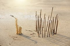 The golden alto saxophone stands on the sand next to the incense. Romantic musical background. Musical cover, creative, relaxation royalty free stock photography