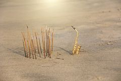 The golden alto saxophone stands on the sand next to the incense. Romantic musical background. Musical cover, creative, relaxation royalty free stock photo