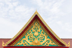 Golden ancient texture on emerald wall infront of temple roof. Stock Photo