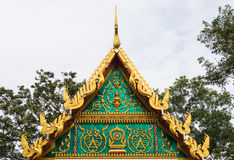 Golden ancient texture on emerald wall infront of temple roof. Stock Photos