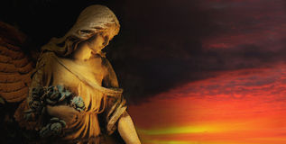 Golden angel on the background of red sky (antique statue) Stock Photography