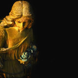Golden angel on the black background (antique statue) Royalty Free Stock Images