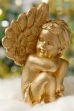 Golden angel figure. On fluffy white material, with blurred lights in the background stock photos