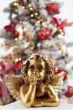 Golden angel figure close up christmas tree in background Royalty Free Stock Images