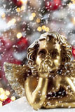 Golden angel figure close up christmas tree in background Royalty Free Stock Photography