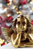 Golden angel figure close up christmas tree in background Stock Photo