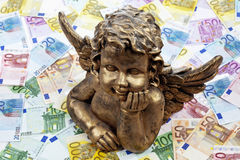 Golden angel sculpture on heap of euro notes Royalty Free Stock Photography
