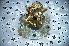 Golden angel with stars. Golden cherub in the middle of stars Stock Photo
