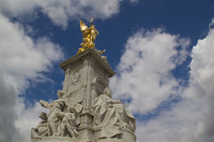 Golden angel statue on Queen Victoria monument in London. Golden winged angel above stone memorial to Queen Victoria outside Buckingham Palace in Westminster Royalty Free Stock Photography
