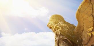 Golden angel in the sunlight antique statue