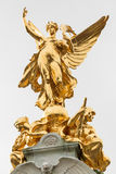 Golden angel of Victoria Memorial. The golden angel with two seated figures on top of the Victoria Memorial in front of Buckingham Palace, London, UK Stock Photos