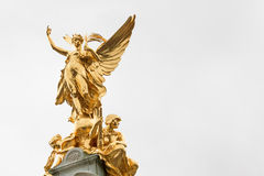 Golden angel of Victoria Memorial. The golden angel with two seated figures on top of the Victoria Memorial in front of Buckingham Palace, London, UK Royalty Free Stock Image