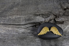Golden angel wings on a black stone with grey wooden background. Stock Image