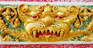 Golden angry face of giant statue on ceramic wall at temple Stock Photo