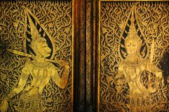 Golden antique drawing of Thai guardian angels on temple door Royalty Free Stock Photo