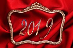 Golden 2019 in a antique frame with red silk background. Golden 2019 numbers in a antique frame with red silk background stock image