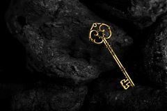 Golden Antique Key on Black Stone Background stock photos