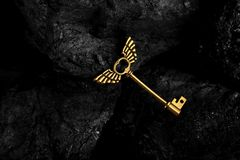 Golden Antique Key with Wings on Dark Black Background stock photo