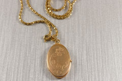 Golden antique locket. On embossed silver paper Stock Photo